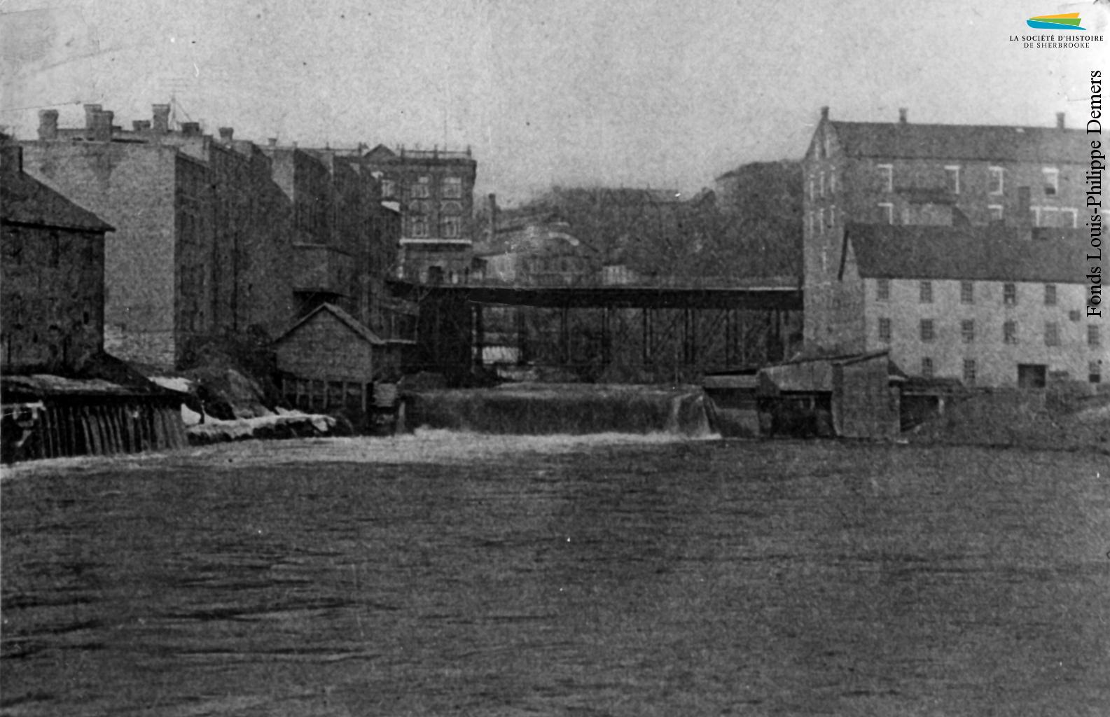 Le site du confluent vers 1898, avec le pont Gilbert-Hyatt et la rue Dufferin. L'usine Sherbrooke Iron Works est située dans le bâtiment blanc à l'avant-plan à droite. Elle y reste jusqu'en 1912.