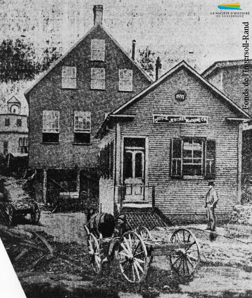 Les premières installations occupées par la Jenckes, entre 1887 et 1890. Situés entre la rue Bank et la rivière Magog, les bâtiments sont la propriété de la compagnie Smith Elkins jusqu'à sa faillite en 1887.