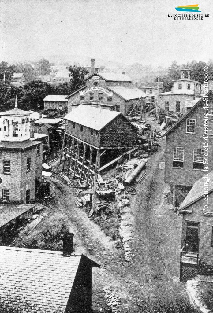 La Jenckes Machine Company (à l'arrière, au centre de la photo), située entre la rue Bank et la rivière Magog, en 1890. À l'origine installée sur la rue <em>Factory</em> (Frontenac), la compagnie emménage sur ce site en 1887.