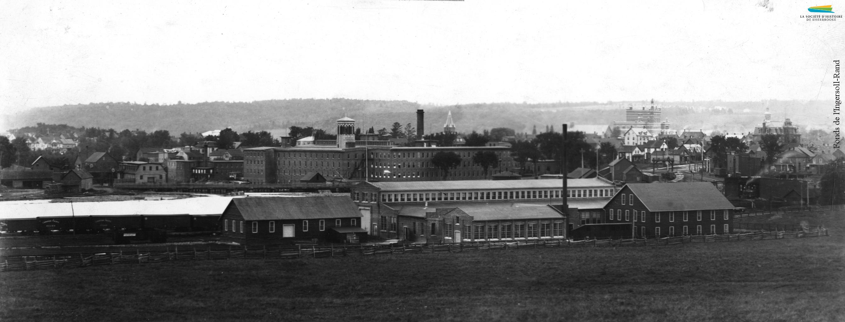 Les premiers bâtiments du complexe industriel de la <em>Rand</em>, à proximité des rues Galt et Belvédère, vers 1901. La rivière Magog et l'usine Paton sont visibles à l'arrière-plan.