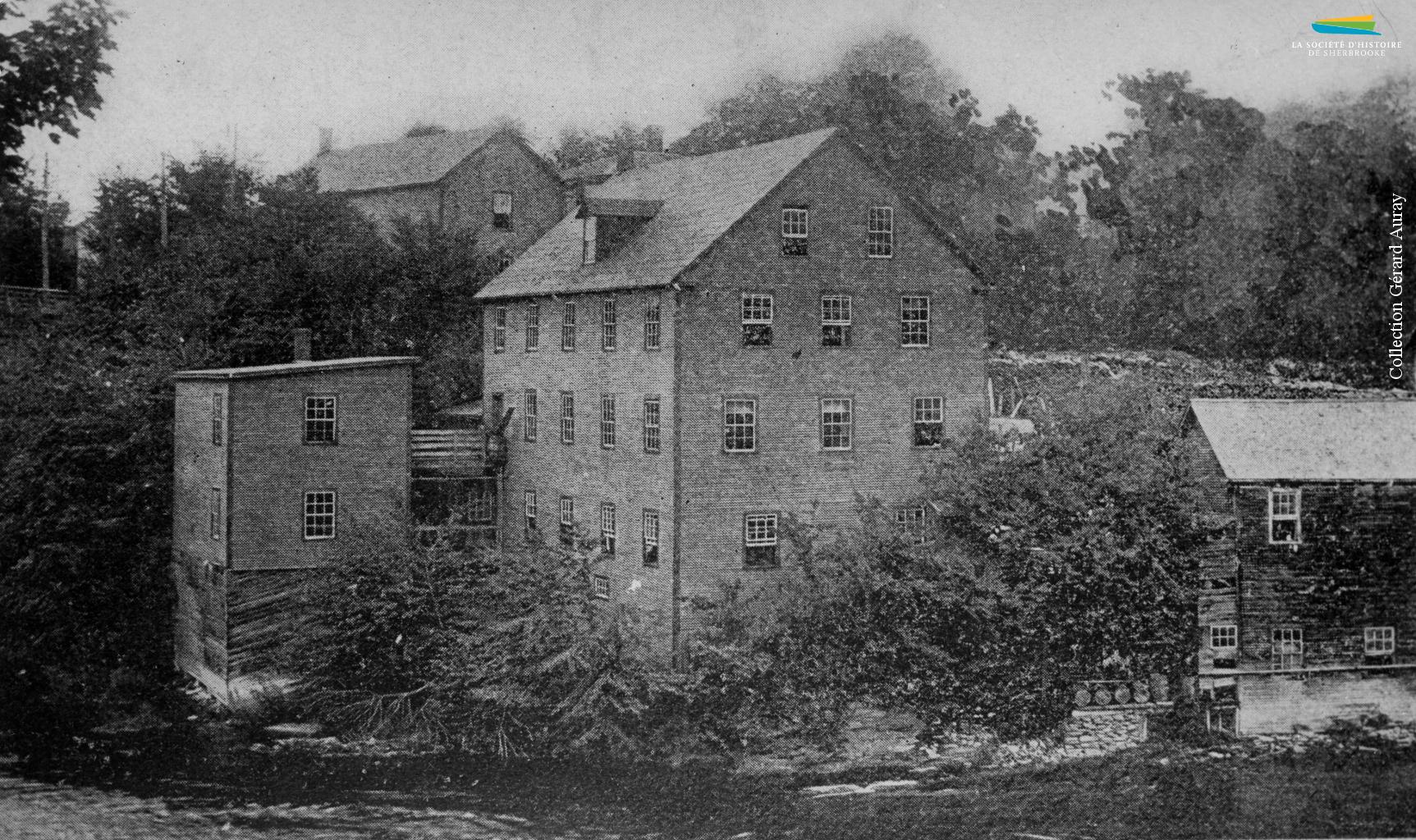 La compagnie <em>Magog Woollen Mills</em>, sur la rivière Magog, vers 1898. Établie par A.L. Grindrod en 1868, elle devient ensuite la propriété de la famille Lomas jusqu'à sa fermeture en 1924.