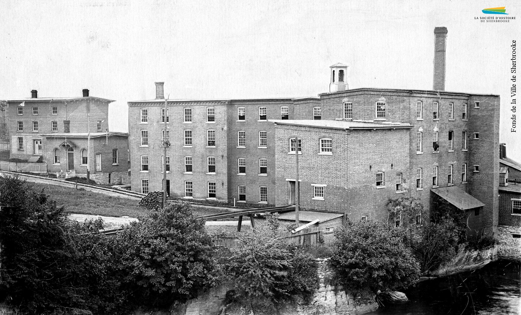 Vue de l'arrière des bâtiments de la manufacture de laine d'Adam G. Lomas, située entre la rue Belvédère Nord et la rivière Magog, en 1898.