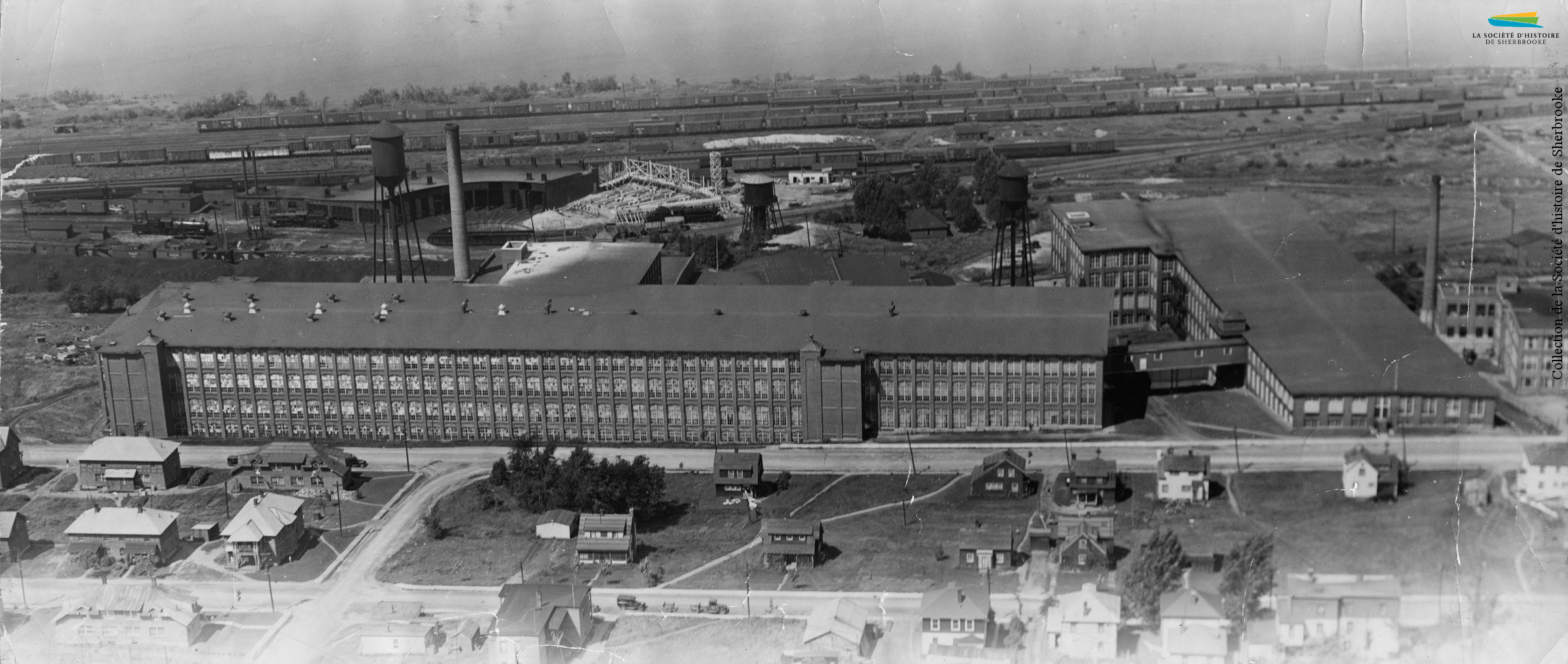 Le coton effectue un retour à Sherbrooke en 1918-1919, lorsque la compagnie <em>Canadian Connecticut Cotton Mills</em> y construit une usine, rue du Pacifique. Elle y fabrique des toiles de pneu en coton. L'usine est rachetée en 1928 par la <em>Dominion Textile Co.</em> La compagnie est marquée par plusieurs grèves entre 1936 et 1938; l'attitude patronale envers ses employés engendre d'ailleurs le déclenchement d'une Commission royale d'enquête sur l'industrie du textile en 1936. Les usines de Sherbrooke ferment progressivement entre 1994 et 2002. Photo : L'usine de la <em>Dominion Textile</em>, installée entre la voie ferrée et le quartier ouvrier (1937).