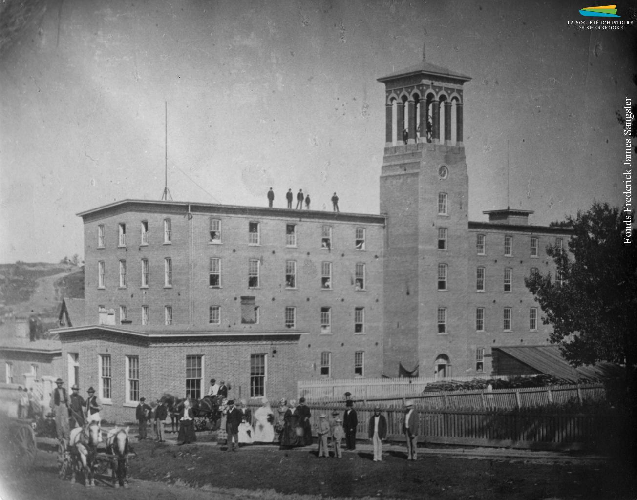 Photographie prise le jour de l'inauguration de l'usine de textiles Paton, en juillet 1867. Plusieurs bâtiments s'ajoutent au complexe au cours des années suivantes et, en 1892, la Paton devient la plus grande usine de lainages au Canada.