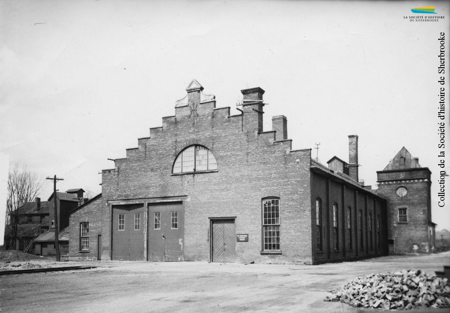 Construit pour l'usine de viande de la <em>Canadian Meat & Produce Company</em> en 1875, le bâtiment est acheté par le <em>Quebec Central railway</em> en 1882. De 1940 à 1946, il servira de camp d'internement pour des ressortissants allemands. Photo: années 1910.