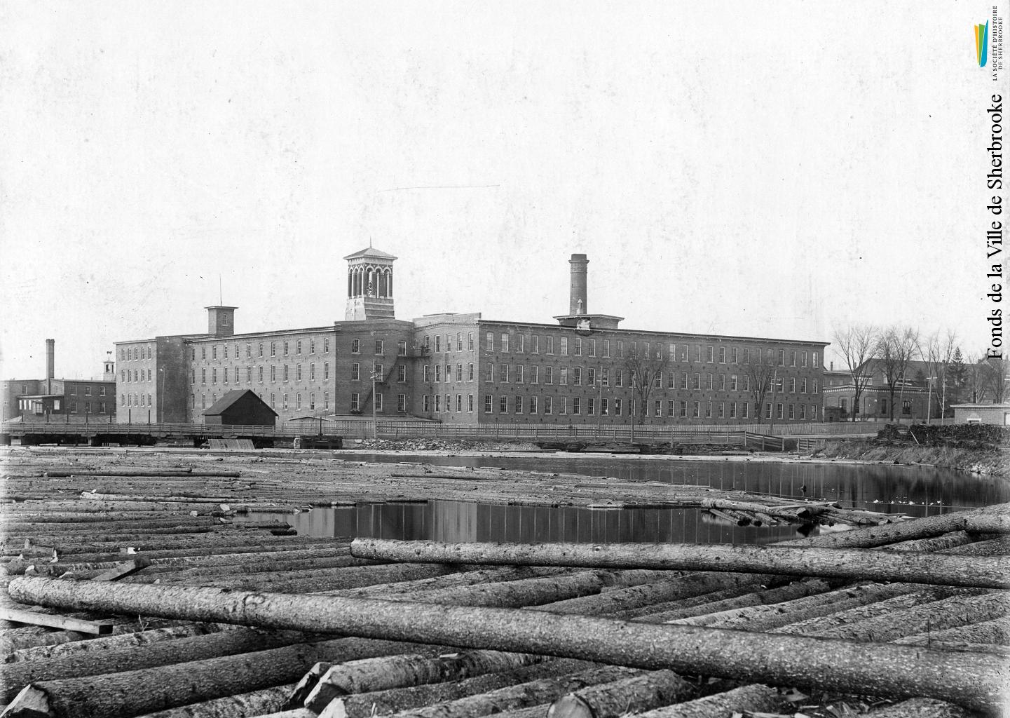 La rivière Magog recouverte de billots de bois, destinés à la scierie de la <em>British American Land Company</em>, en 1898. À l'arrière, les bâtiments de la Paton.