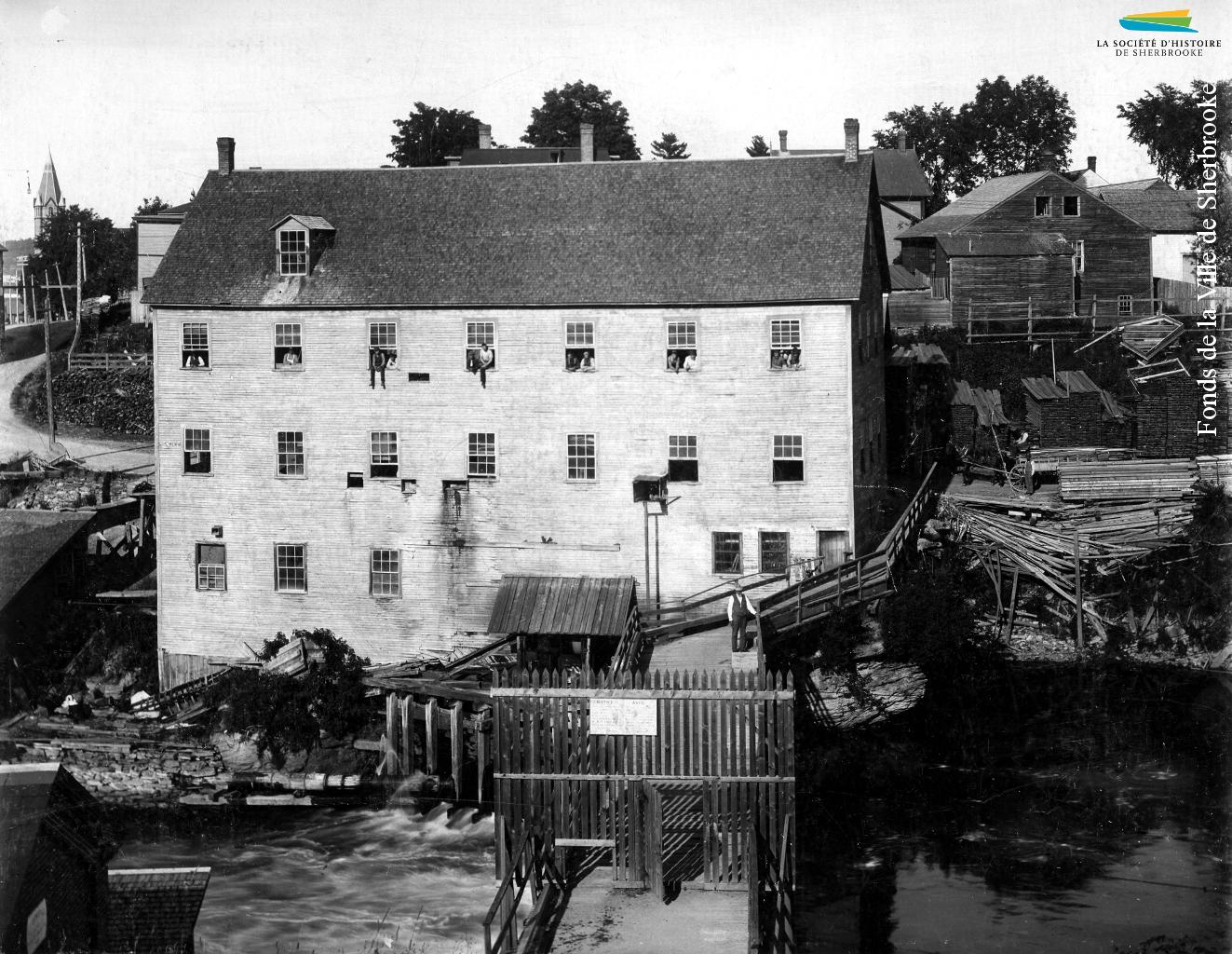 L'arrière de la manufacture de portes et fenêtres de <em>G.G. Bryant & Co.</em>, en 1890. Le bâtiment est situé le long de la rue Belvédère Nord, vis-à-vis du barrage no 2, visible au bas de la photographie.