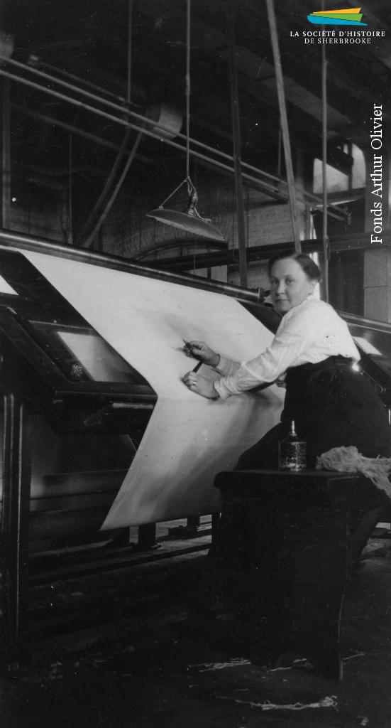 Une femme inspecte une pièce de coton à la Canadian Connecticut Cotton Mills, vers 1928. La majorité de la main-d'œuvre de la plupart des usines de textiles de Sherbrooke est féminine.