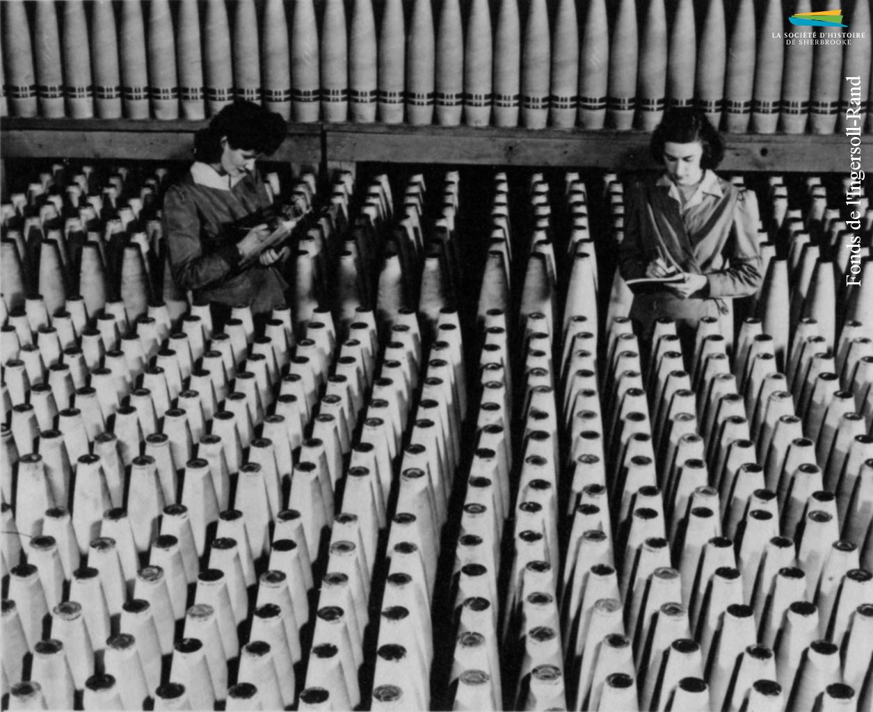 Deux ouvrières de l'Ingersoll-Rand circulent au milieu d'obus, entre 1939 et 1945. L'usine de Sherbrooke reçoit plusieurs commandes de munitions pendant la Seconde Guerre mondiale de la part du gouvernement canadien. Un grand nombre de femmes y sont embauchées.