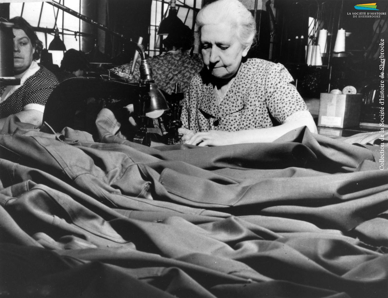 Des femmes travaillent à la confection d'uniformes, pendant la Seconde Guerre mondiale (1939-1945). À Sherbrooke, les manufactures de tissus (Paton, Dominion Textile) et de vêtements (S. Rubin Ltd) reçoivent de telles commandes du gouvernement canadien.