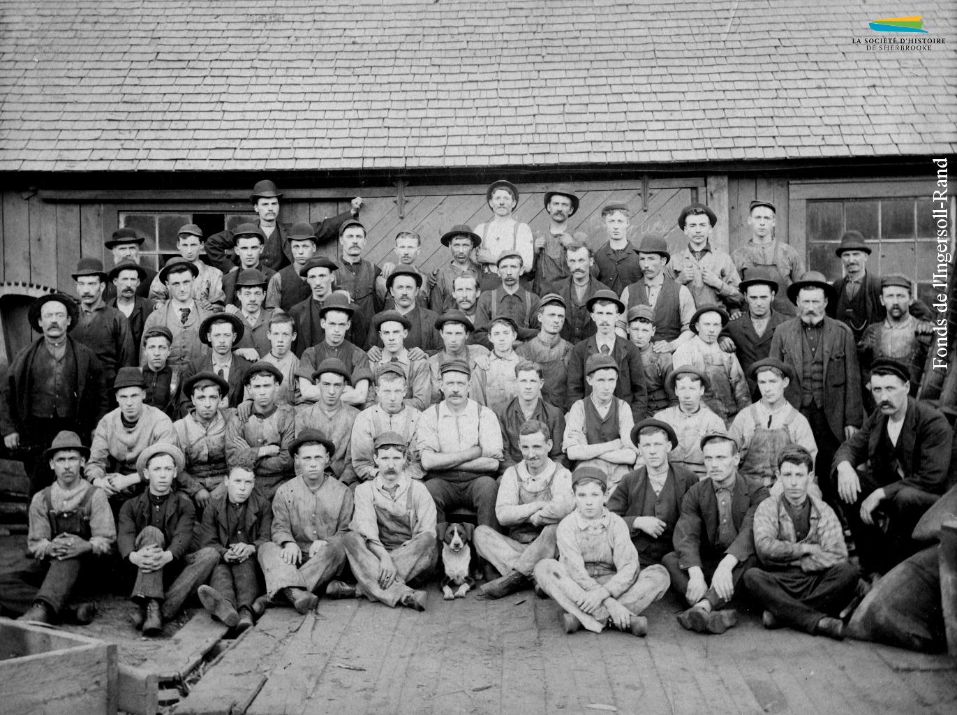 Des ouvriers de la compagnie Jenckes Machine prennent la pause, devant un bâtiment qu'elle occupe près de la rue Bank. Ce sont surtout des hommes qui travaillent dans la métallurgie, parfois âgés d'à peine 13 ou 14 ans.