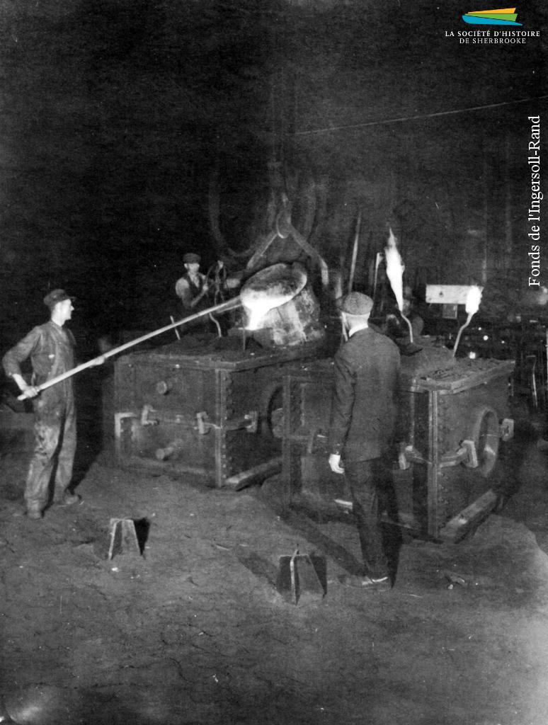 Des ouvriers à l'œuvre dans une fonderie de l'Ingersoll-Rand, en 1939. Du métal en fusion est versé dans un moule.