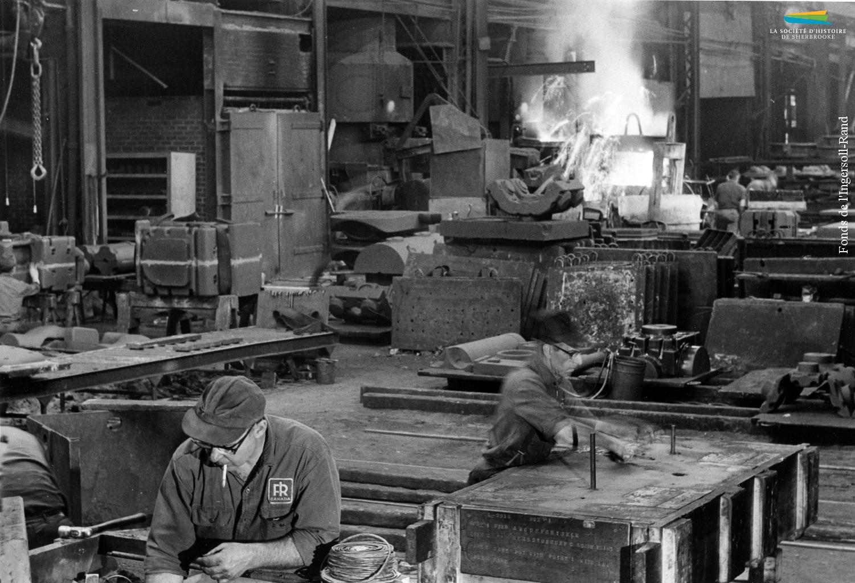 Une photographie prise à l'intérieur de la fonderie de l'Ingersoll-Rand en 1968. Notez l'homme à l'avant-plan qui travaille avec une cigarette à la bouche.