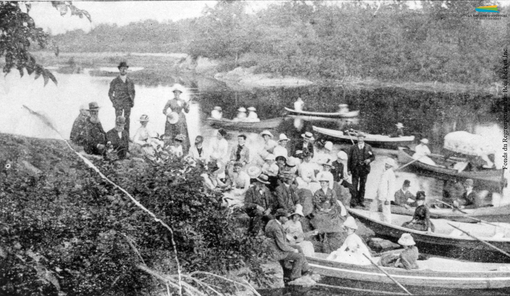 Un groupe de personnes participent à un pique-nique sur les bords de la rivière Saint-François, à proximité de Melbourne, vers 1890. Plusieurs industriels de Sherbrooke organisent chaque année de telles expéditions pour leurs ouvriers.