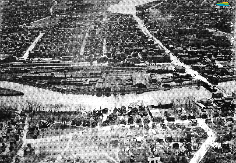 Une vue aérienne du quartier Centre et de la rue King depuis l'est de Sherbrooke, vers 1950. Au centre se trouve le complexe industriel construit par la <em>Jenckes Machine Co.</em> en 1894, et tout autour des habitations.