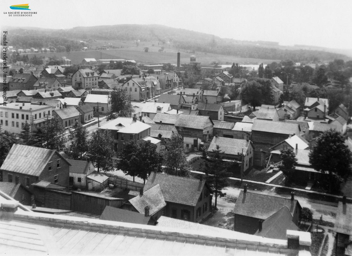 Photographie de la rue Marquette prise depuis le toit du Séminaire, avec la Paton et le Mont Bellevue à l'arrière-plan, vers 1906. La British American Land Company trace cette rue et les autres du Plateau-Marquette dès 1835, ce qui en fait le plus vieux quartier ouvrier de Sherbrooke.