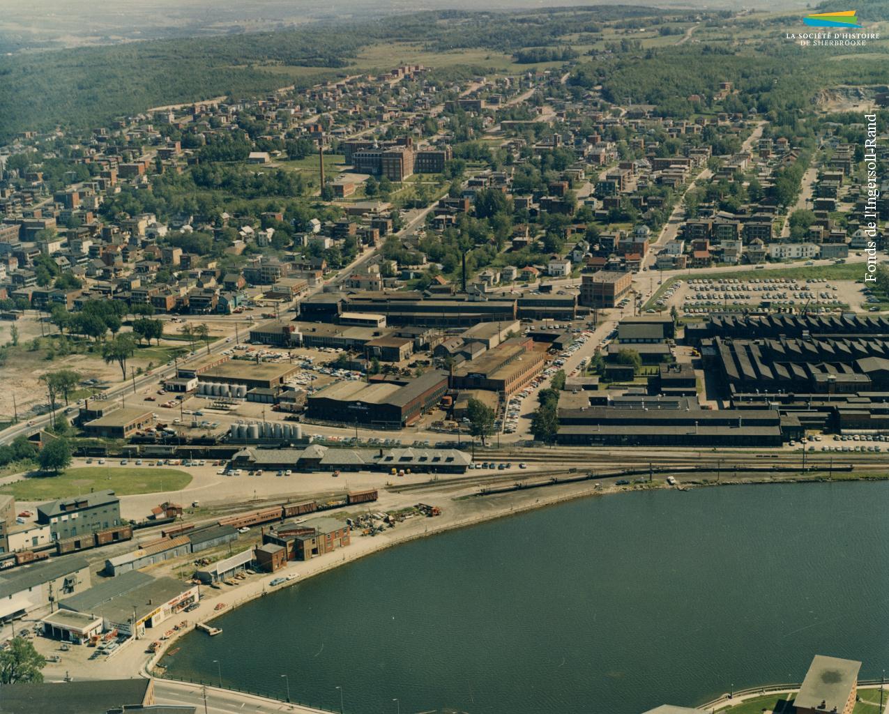 Vue aérienne du quartier Ouest en 1963. À l'avant-plan se trouvent les usines métallurgiques et la gare du Canadien Pacifique avec, derrière, les rues résidentielles.