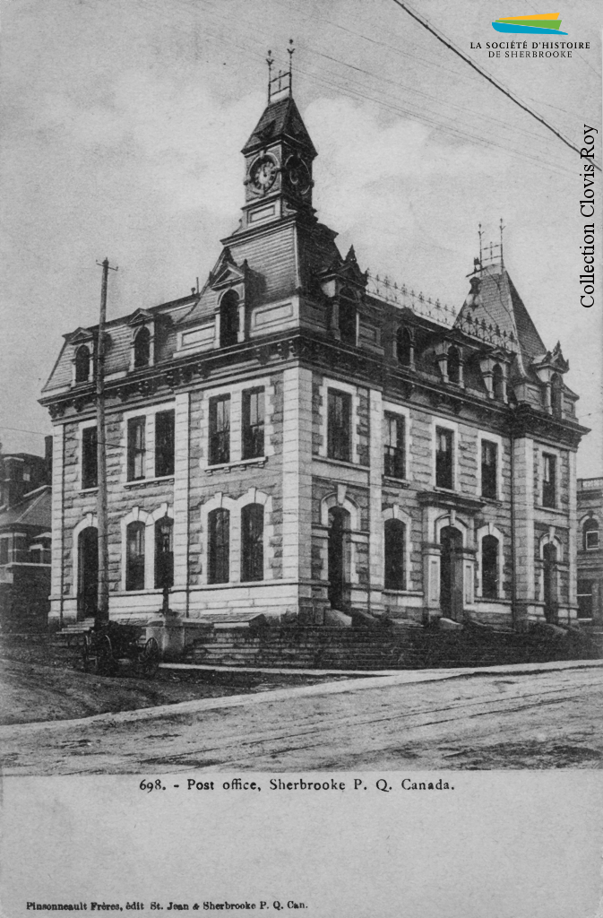 Le bureau de poste de Sherbrooke, vers 1905. Construit en 1885, il garde cette fonction jusqu'en 1953 et devient alors la bibliothèque municipale. Au moment de sa construction, le courrier est transporté par train, mais avant l'arrivée du chemin de fer ce sont des diligences qui assurent ce service à partir de Québec ou de Boston.