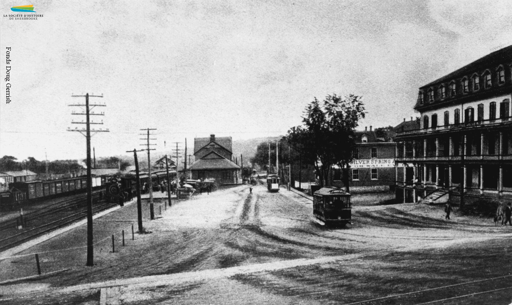 La rue <em>Depot</em> (du Dépôt) en 1897 ou 1898. La gare Union se trouve sur le site de la première gare de Sherbrooke, construite pour accueillir le premier train en 1852. La rue est aussi le centre du réseau de tramway de la ville, les visiteurs arrivant systématiquement en train.