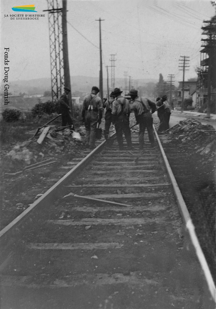 Des ouvriers s'affairent à poser des rails de tramway dans une rue de Sherbrooke, vers 1921. Il s'agit sans doute de la ligne Fairmount, complétée cette même année, qui lie le centre-ville aux rues situées près de la Dominion Textile et de l'Ingersoll-Rand.
