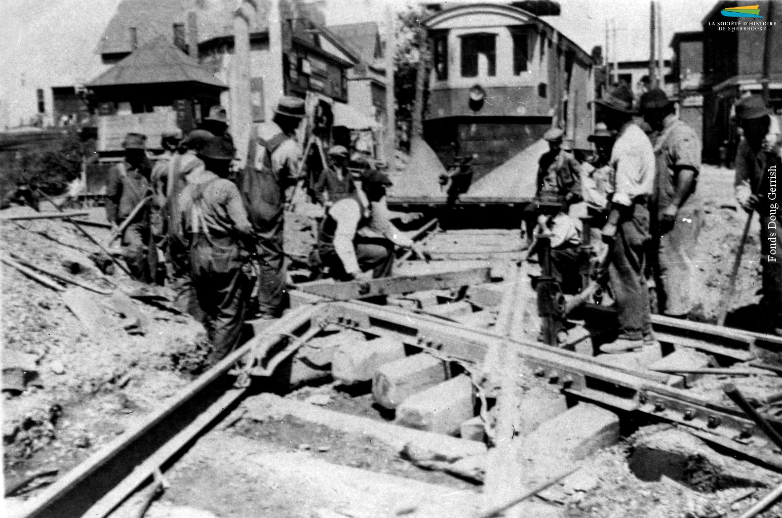 Des travaux sont effectués sur une ligne de tramway, là où les rails du Canadien Pacifique croisent la rue Alexandre, vers 1920. Ces travaux sont probablement effectués dans le cadre de la construction de la ligne Fairmount, qui se rend dans le quartier Ouest.