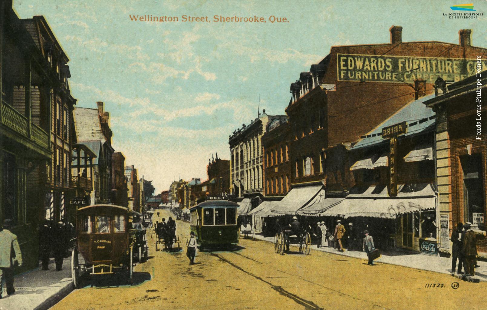 La rue Wellington Nord dans les années 1910. Un tramway, des voitures tirées par des chevaux et des piétons circulent sur la rue, qui est alors la principale artère commerciale de Sherbrooke.