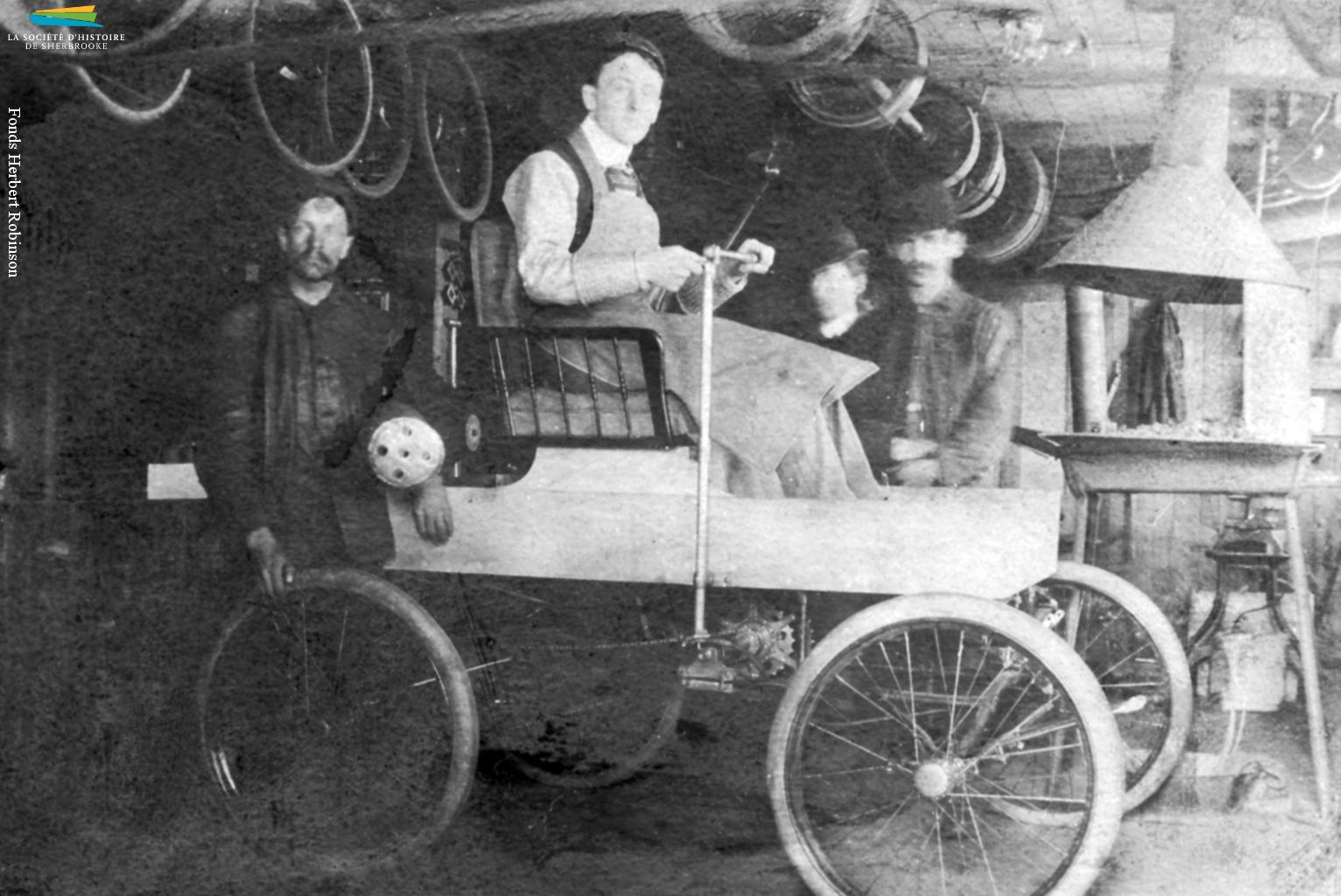 La première voiture à essence construite au Canada serait l'œuvre du Sherbrookois George Foote Foss, qui l'aurait mise au point en 1897. Sur cette photo on voit M. Foss sur sa <em>Fossmobile</em> dans son atelier. Un autre habitant de Sherbrooke, Joseph Fréchette, construit lui aussi une automobile en 1901, et une seconde en 1902.