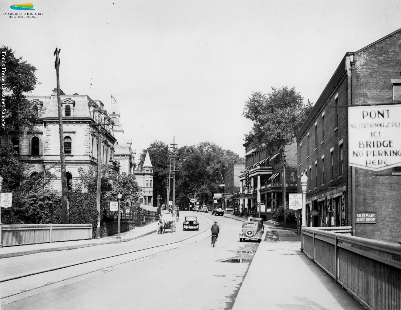 La rue Dufferin vers 1934. Les tramways ne circulent plus depuis deux ans, mais il faut attendre 1936 pour que les rails soient finalement enlevés. Et malgré la multiplication des automobiles, certains se déplacent encore en fiacres tirés par des chevaux...