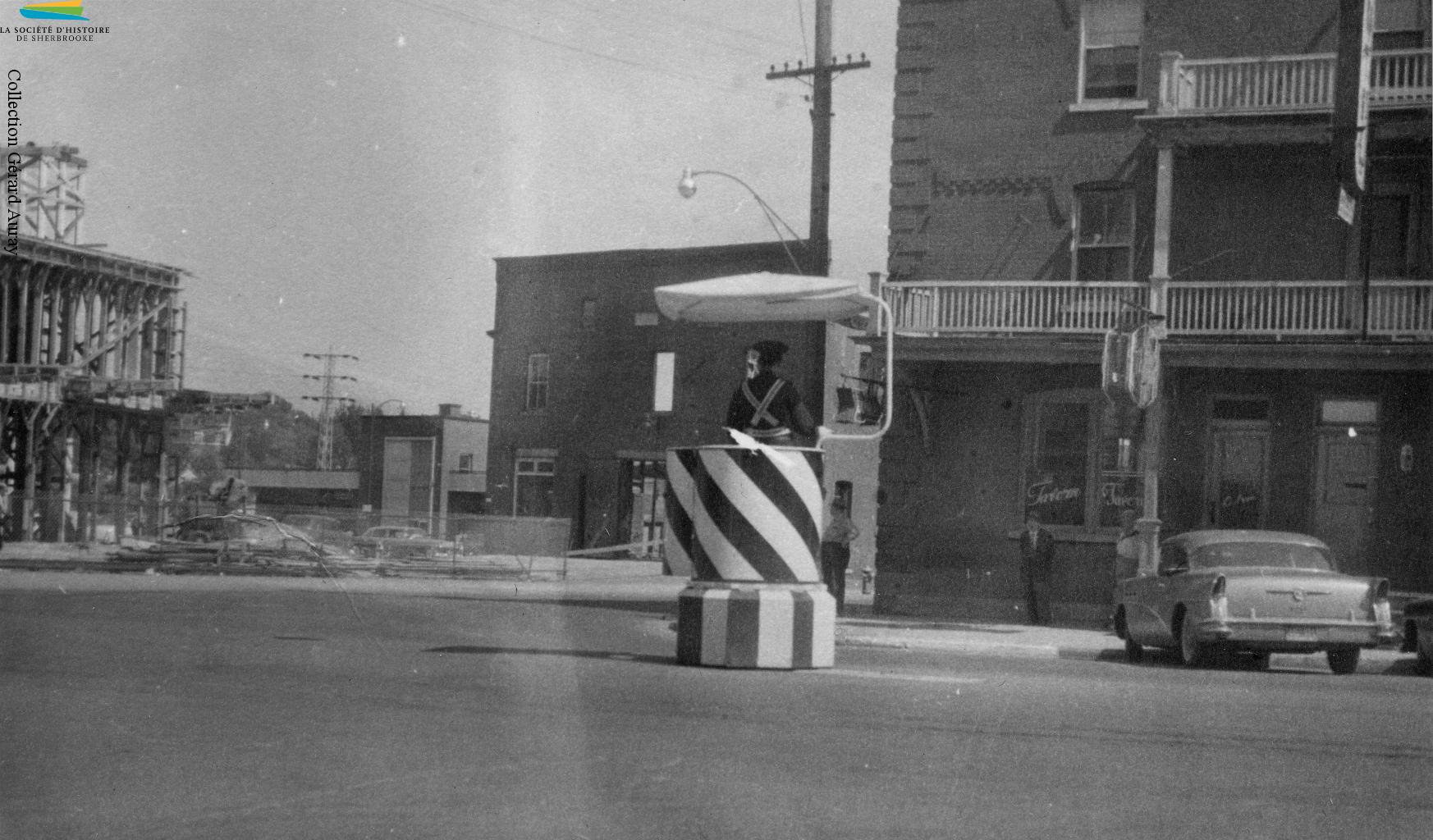 Un policier dirige la circulation au coin des rues King Ouest et Grandes-Fourches, vers 1957. Malgré la présence de feux de circulation depuis 1930, ces policiers restent présents sur certains carrefours routiers de Sherbrooke jusque dans les années 1970.