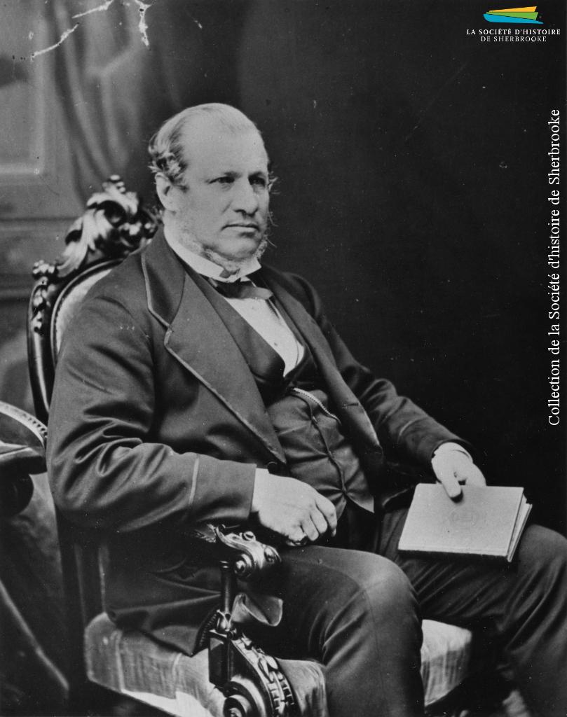 Alexander T. Galt (1817-1893) en 1869. Originaire de Grande-Bretagne, il arrive au Canada vers 1835 comme employé de la BALCo, dont il devient éventuellement le commissaire. Il lance aussi sa carrière politique en 1852, ce qui l'amène à travailler à la création du Canada en 1867, et en devient le ministre des Finances.