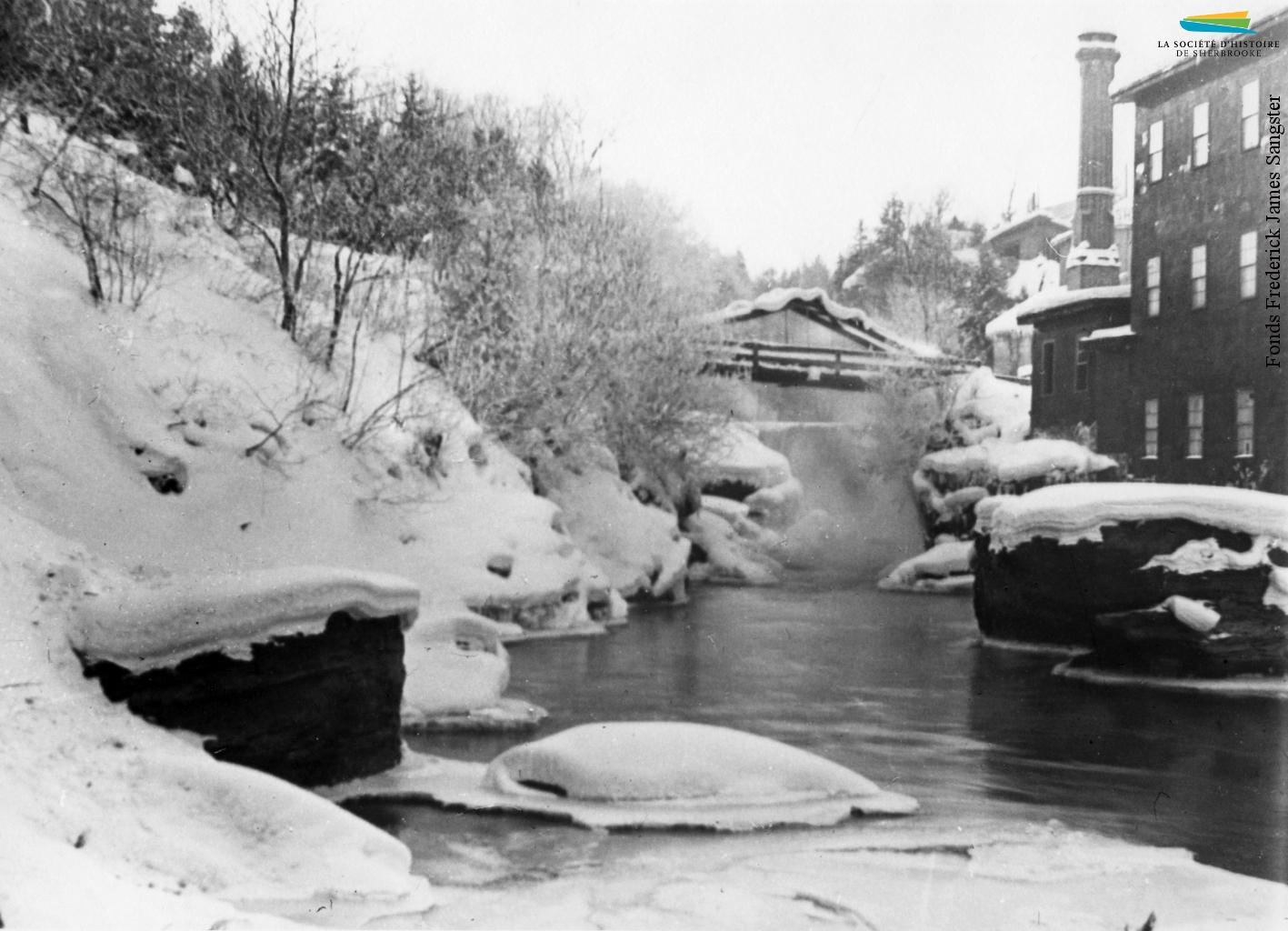 La rivière Magog en hiver, vers 1900. Son fort débit fait en sorte que l'eau ne gèle pas et qu'elle peut alimenter en énergie hydraulique les manufactures situées sur ses rives. Après l'adoption de l'électricité comme principale source d'énergie, ce sont les centrales hydroélectriques qui sont alimentées toute l'année.