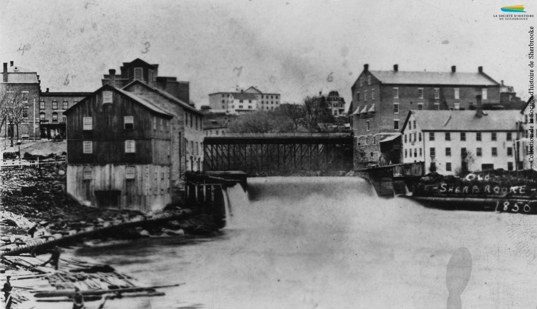 Le barrage no 5 et le confluent des rivières Magog et Saint-François, vers 1885. Le barrage alimente en eau les moulins logés dans les bâtiments situés sur les deux rives. L'eau est alors la principale source d'énergie pour les manufactures de la ville, ce pour quoi celles-ci sont concentrées le long de la rivière Magog.
