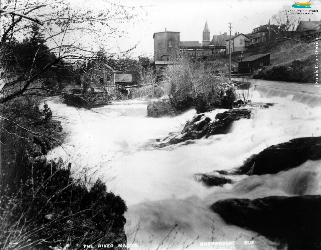 La rivière Magog et la centrale Frontenac (le bâtiment à gauche), vers 1896. Le barrage no 3, hors champs, sert à approvisionner en eau les moulins et manufactures situés à proximité. Il est converti en 1888 pour produire de l'électricité, une source d'énergie adoptée progressivement par les manufactures de Sherbrooke. L'eau sert encore de source d'énergie pendant quelques décennies.