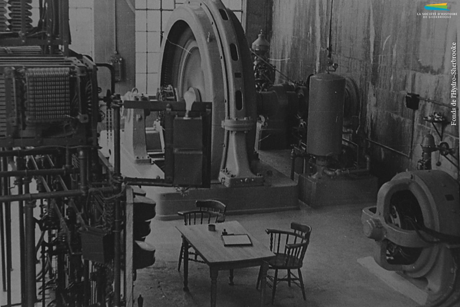 La salle des génératrices de la centrale hydroélectrique de Weedon, en 1942. Le barrage et la centrale sont achetés en 1917 par la Ville de Sherbrooke, qui construit une ligne de transport de l'électricité à Sherbrooke. Le barrage et la centrale sont reconstruits en béton en 1920-1921.