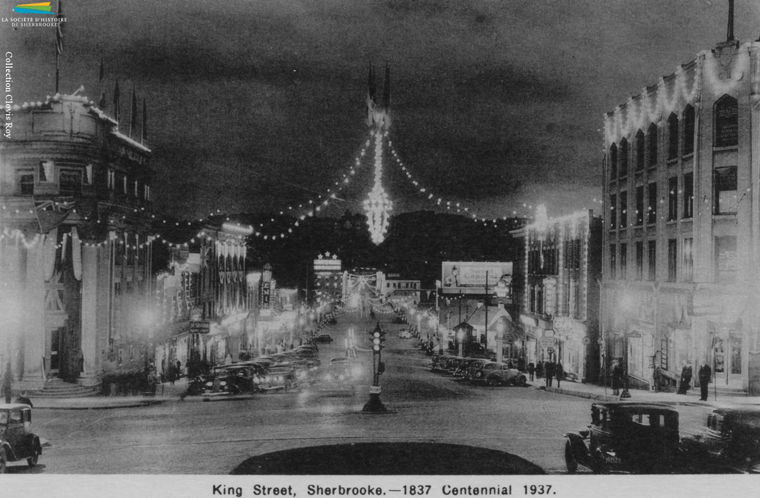 Des photos du centre-ville de Sherbrooke, tout éclairé à l'occasion du « centenaire » de 1937. Les autorités municipales cherchent à stimuler le tourisme et la venue d'industries, entre autres en vantant ses ressources hydroélectriques, et montent de toutes pièces des célébrations du centenaire même si l'année 1937 ne marque le centième anniversaire de rien de significatif...